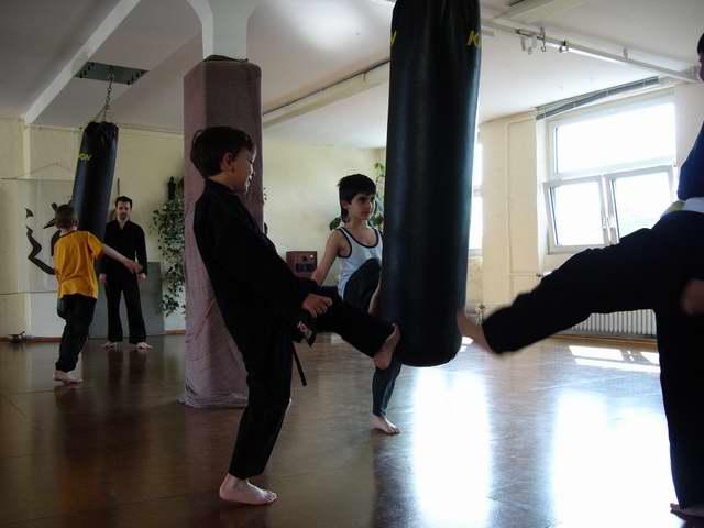 Selbstverteidigung am Sandsack Kinder üben Ihre Tritte nach vorne in der Gruppe